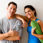 Man and woman at gym in fitness attire holding water bottles and yoga mat standing against wall smiling.